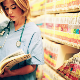 A nurse flips through a medical document.