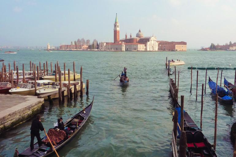 A photo of Gondoliers rowing their boats while Venice, Italy stretches in the horizon