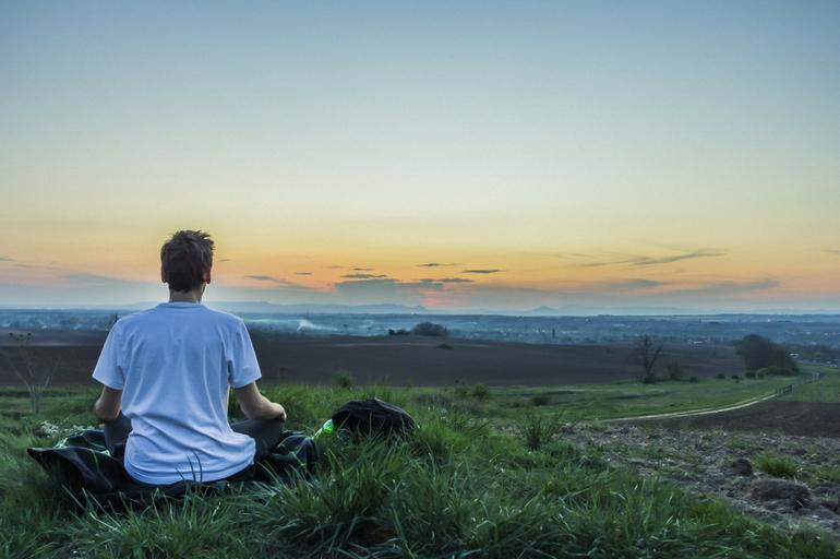 Person meditating in field at dawn