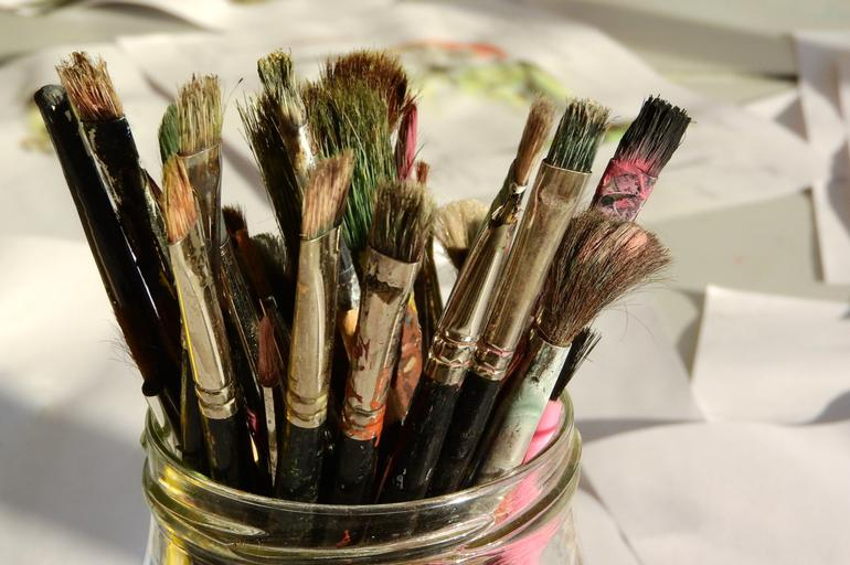 A group of dirty paint brushes sitting in a mason jar